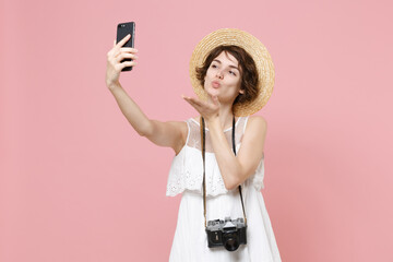 Cute tourist girl in dress hat photo camera isolated on pink background. Traveling to travel weekends getaway. Air flight journey concept. Doing selfie shot on mobile phone, blowing sending air kiss.