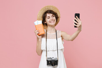 Smiling tourist girl in dress hat with photo camera isolated on pink background. Traveling abroad weekend getaway. Air flight journey concept. Hold passport tickets doing selfie shot on mobile phone.