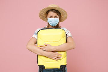 Sad traveler tourist girl in striped shirt hat sterile face mask isolated on pink background. Epidemic pandemic rapidly spreading coronavirus 2019-ncov sars covid-19 flu virus concept. Hold suitcase.