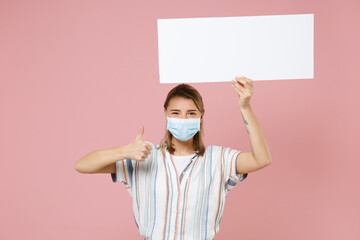 Young girl in casual striped shirt sterile face mask isolated on pink background. Epidemic pandemic coronavirus 2019-ncov sars covid-19 flu virus concept. Hold board with place text showing thumb up.