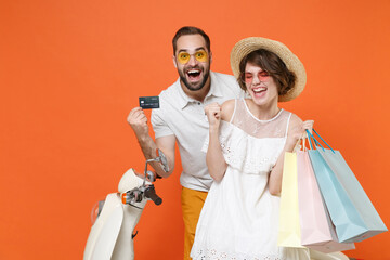 Happy couple friends guy girl in hat glasses sit on moped isolated on orange background. Driving motorbike transportation concept Hold package bag with purchases credit bank card doing winner gesture.