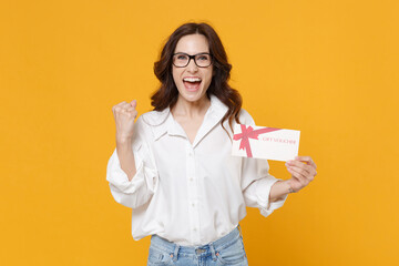 Happy young brunette business woman in white shirt glasses isolated on yellow background. Achievement career wealth business concept. Mock up copy space. Hold gift certificate, doing winner gesture.