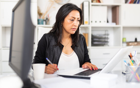 Busy female entrepreneur in office with papers and laptop