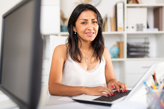 Smiling female office employee working with laptop and documents