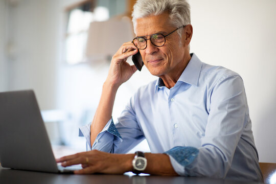 businessman using laptop and phone in office