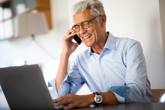 Close up smiling businessman talking with phone while looking at laptop computer