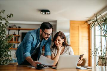 Couple doing finances at home, portrait.