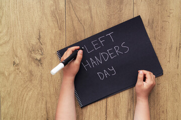 Left-handed child with a marker writes words on a notebook.