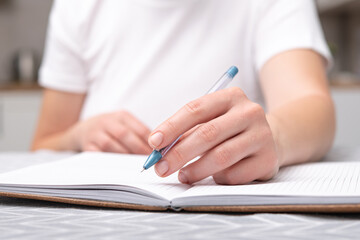 A left-handed woman holds a pen