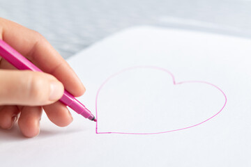 Woman with a marker draws a red heart