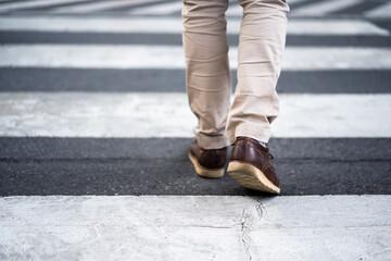 close up legs of man walking cross street in city