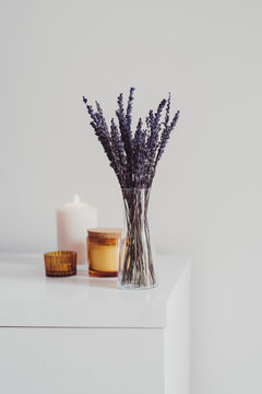 Dried lavender in a small glass vase and aroma candles on white table. Simple Living room decor. Minimal style. Aromatherapy at home