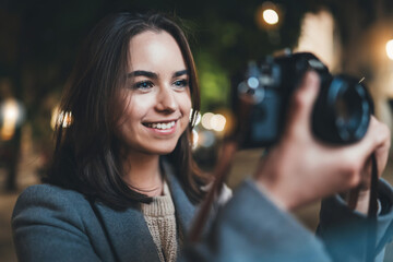 Fotomurales - Photographer tourist girl with retro camera, happy smile woman take photo on background bokeh light in evening city, Blogger photoshoot photo hobby