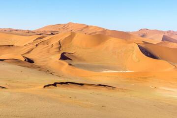 Photo sur Plexiglas Orange eclat Dunas y sus crestas, barlovento y sotavento en una tarde soleada, quietud típica del paisaje del parque nacional Namib-Naukluft, en Namibia