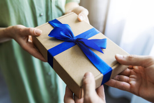 man giving gift box with blue ribbon to woman