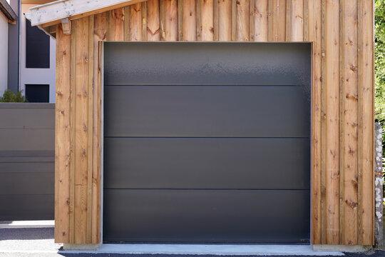 Modern car garage sectional door in dark grey of wooden building house