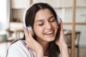 Photo of smiling beautiful woman using wireless headphone