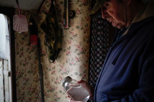 Hanson Rowe, a landowner who blames a leaky gas well on his property for health problems, holds a jar of moonshine in Salyersville