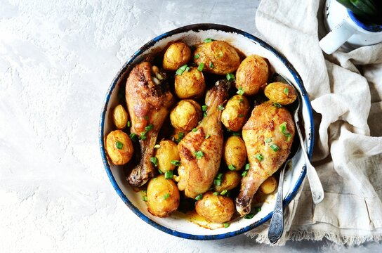 Baked chicken legs with young potatoes in a baking dish on a gray background