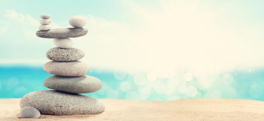 Photo sur Toile Zen pierres a sable Pyramid of sea pebbles on a sunny sand beach