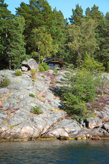 A typical hut on a rock on the seashore in Sweden.