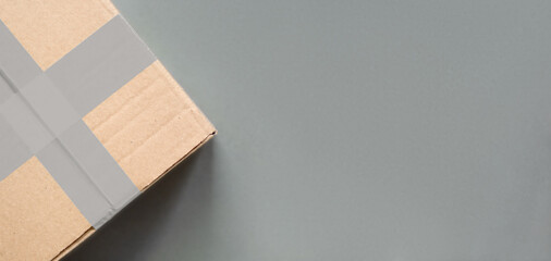 Delivery concept. Cardboard package box closed and sealed on grey background
