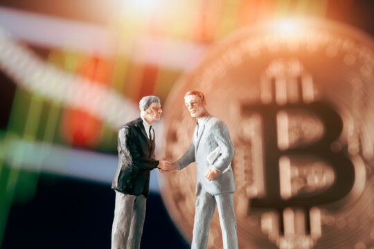 Business agreement concept: Two businessman figurine shaking hands in front of blurry stock market chart and shiny bitcoin. Partnership, success, investment, dealing concept.