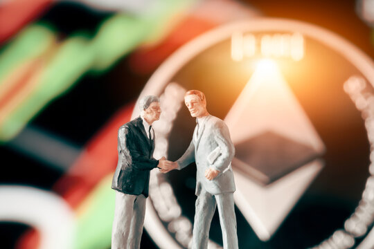 Business agreement concept: Two businessman figurine shaking hands in front of blurry stock market chart and shiny ethereum. Partnership, success, investment, dealing concept.