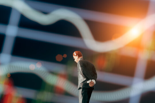 Concept of thinking businessman: Businessman figurine with hands behind back and deciding to make a decision while standing in front of stock market chart on the background.