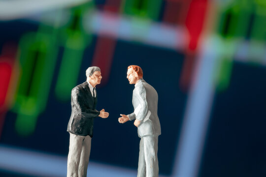 Business agreement concept: Two businessman figurine shaking hands in front of blurry stock market chart. Partnership, success, investment, dealing concept.