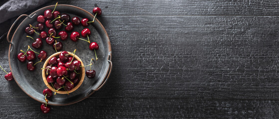 Metallic vintage tray, surface and cup with red juicy cherries inside the cup and scattered around...