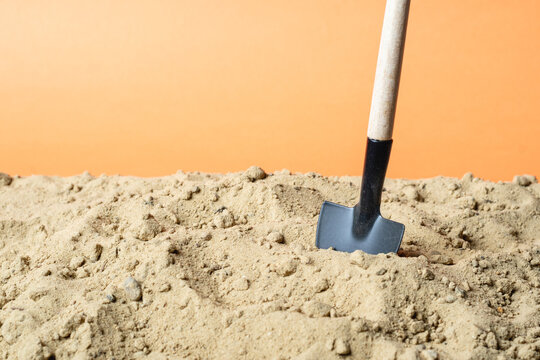 shovel stuck in the sand on an orange background