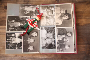 Wall Mural - old retro album with monochrome photos in sepia color and vintage wooden toy clown, concept of genealogy, memory of ancestors, family ties, childhood memories