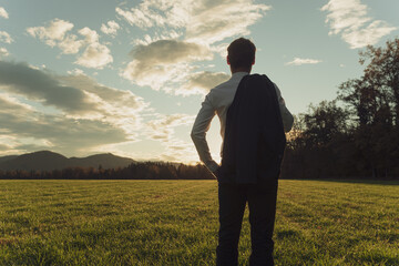 Young businessman standing in autumn meadow gazing into the future Fotomurales