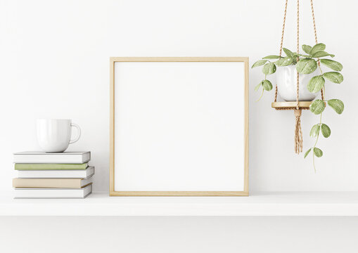 Interior poster mockup with square wooden frame on the shelf with green plant in hanging pot, books, cup and trendy decoration on empty white wall background. 3D rendering, illustration.