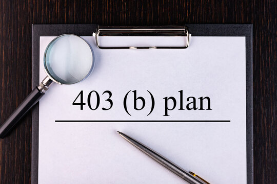 Text 403B Plan is written on a notebook with a pen and a magnifying glass lying on the table. Business concept.