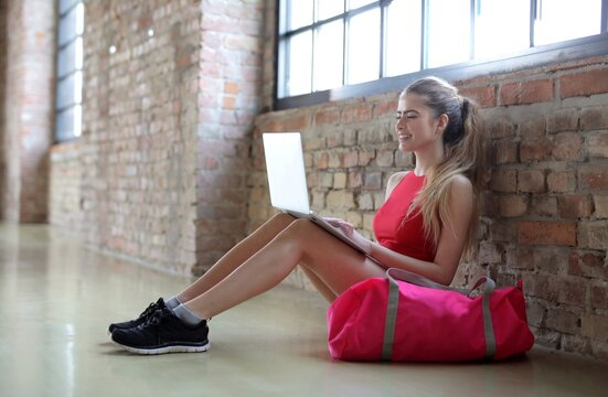 Attractive young female working on the laptop sitting next to her gym bag