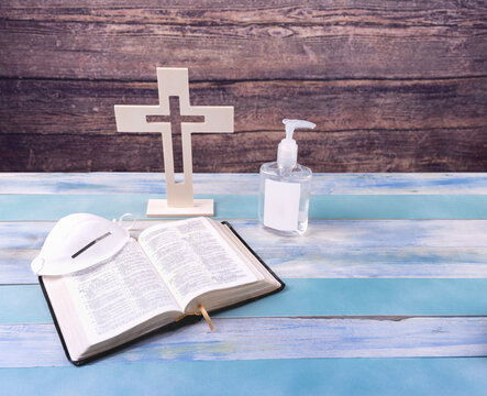 Church with wood cross, face mask, hand sanitizer and bible on vintage wood background. Social distance. Re-opening  of Church. selected focus. Christian concept.