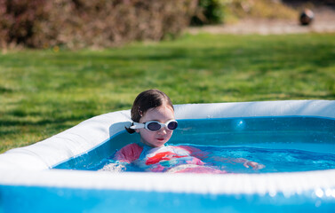 Little girl relaxes in paddling pool in summer