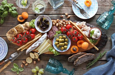 Mediterranean appetizers platter. Diner table with antipasto selection: cured meat and salami,...