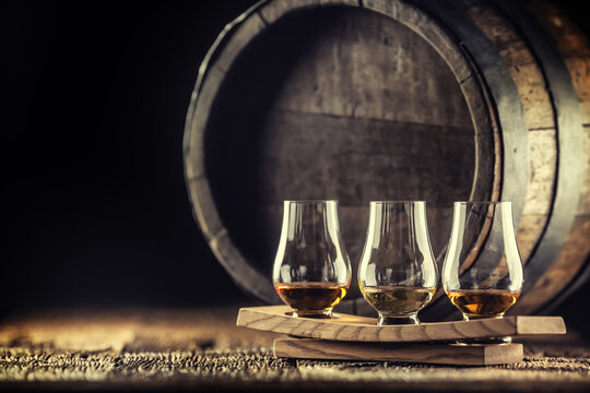 Glencairn whiskey tasting cups on a wooden serving, with a whisky barrel in the dark background
