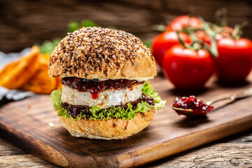 Vegetarian burger with camembert and cranberry sauce on a rustic wooden board