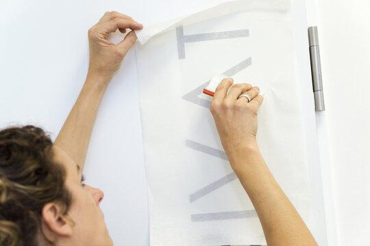 Türfolierung mit Klebebuchstaben / Werbetechnikerin bei der Arbeit