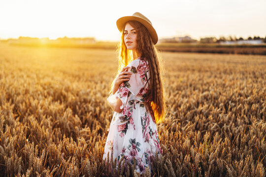 Portrait of a beautiful young woman with curly hair and freckles face. Woman in dress and hat posing in wheat field at sunset and looking at camera