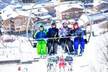 Group of four teen kids sit on the chair lift going to the mountain top on alpine ski resort with houses and station bellow