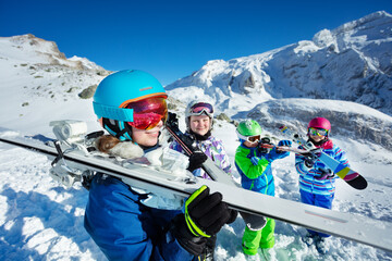 Happy smiling teenage girl in profile with blue helmet and vivid goggles hold ski in her hands in a group of friends children over mountain