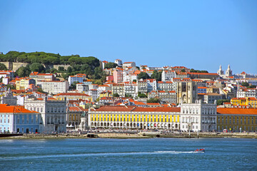 Multi coloured buildings of the old city of Lisbon. São Jorge Castle looking down on the city Praça do Comércio town square in the foreground. View from across the Tagus Estuary, Portugal.