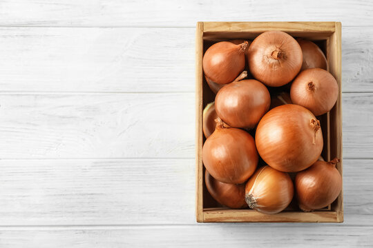 Ripe yellow onion bulbs in crate on white wooden table, top view. Space for text