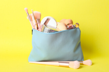Photo sur Toile Inde Cosmetic bag with makeup products and beauty accessories on yellow background