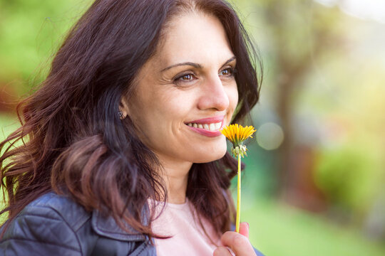 Middle-age woman in black leather jacket smiling, enjoying life, smelling flower